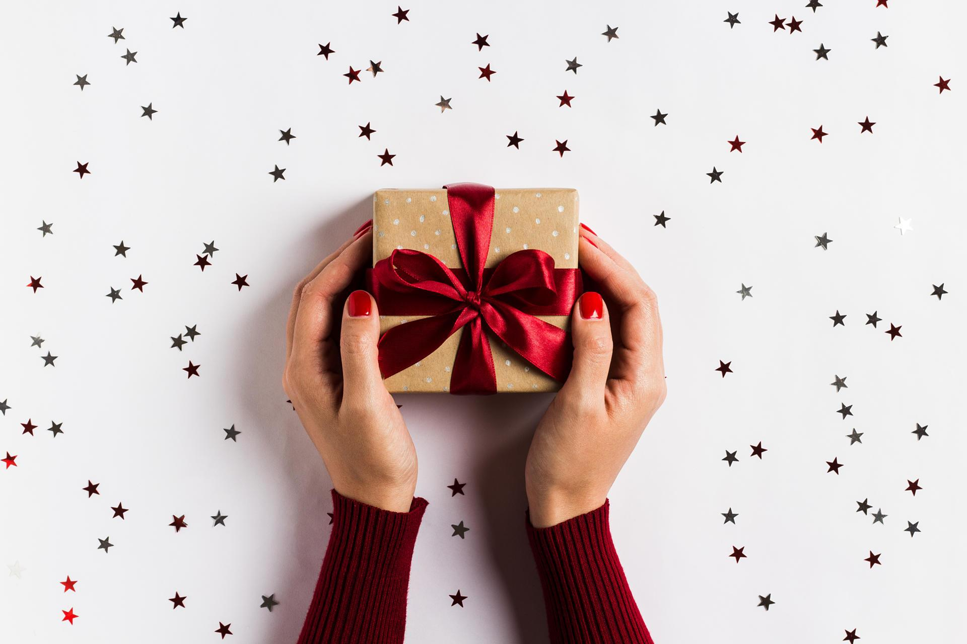 woman-hands-holding-christmas-holiday-gift-box-on-decorated-festive-table.jpg